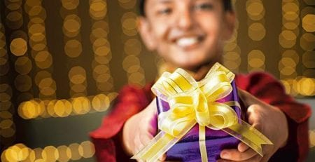 A boy holding a customised gift on Diwali